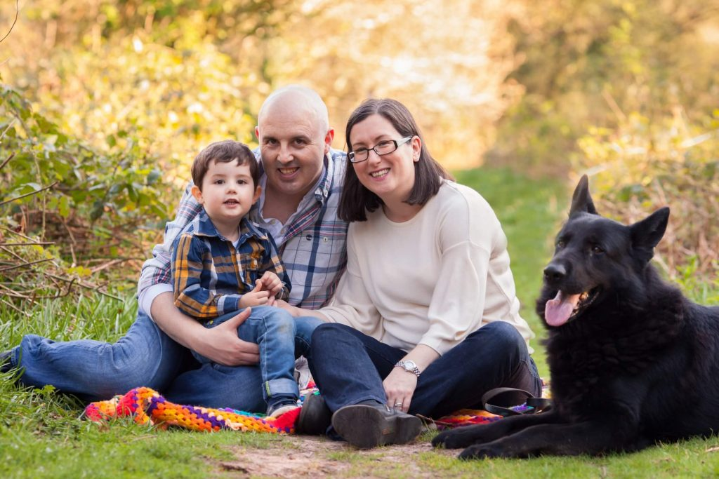 A picture of a family with the mu, dad and little boy sitting on a blanket in a woods with their black german shepherd dog beside them.