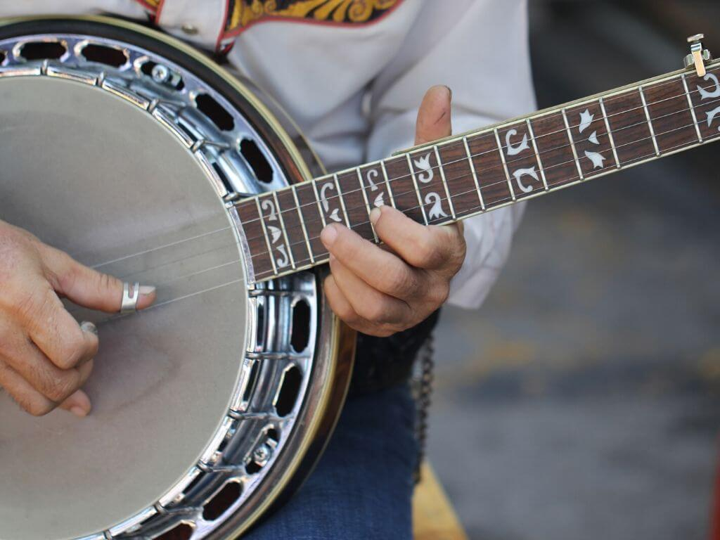 A close-up picture of a mans hands playing a banjo