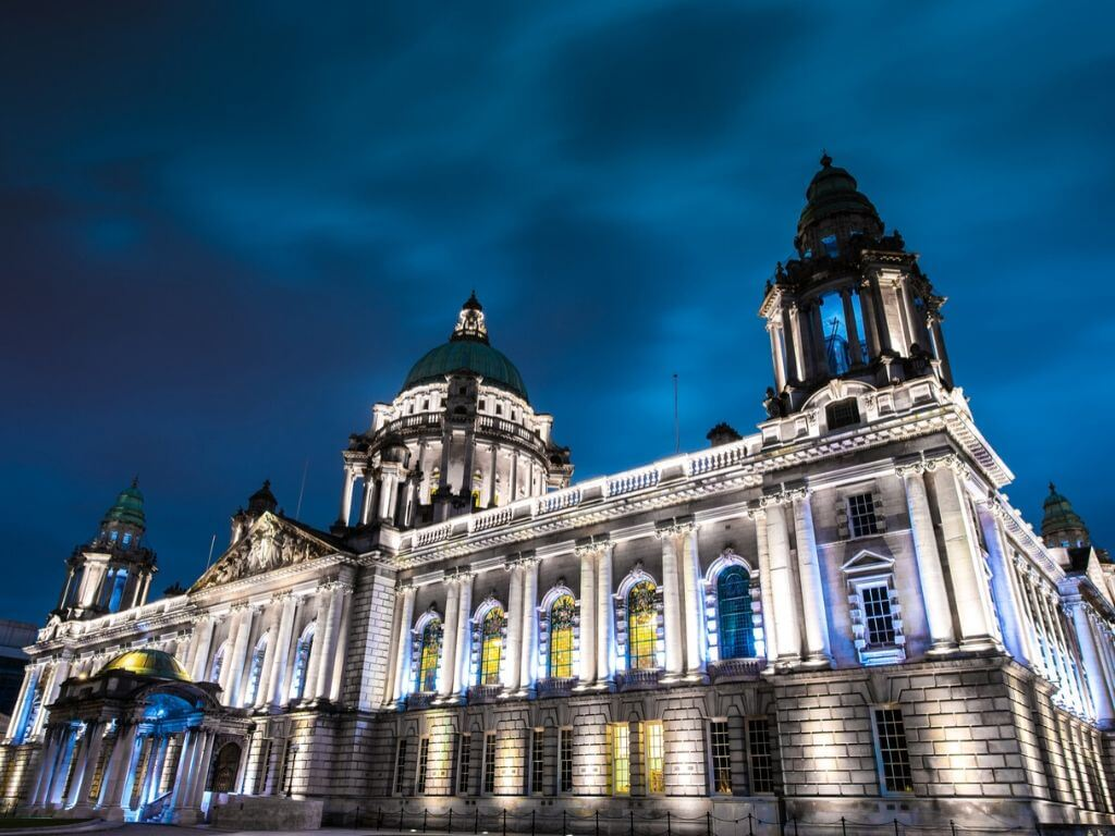 A picture of Belfast City Hall lit up at night time with a navy blue sky above it