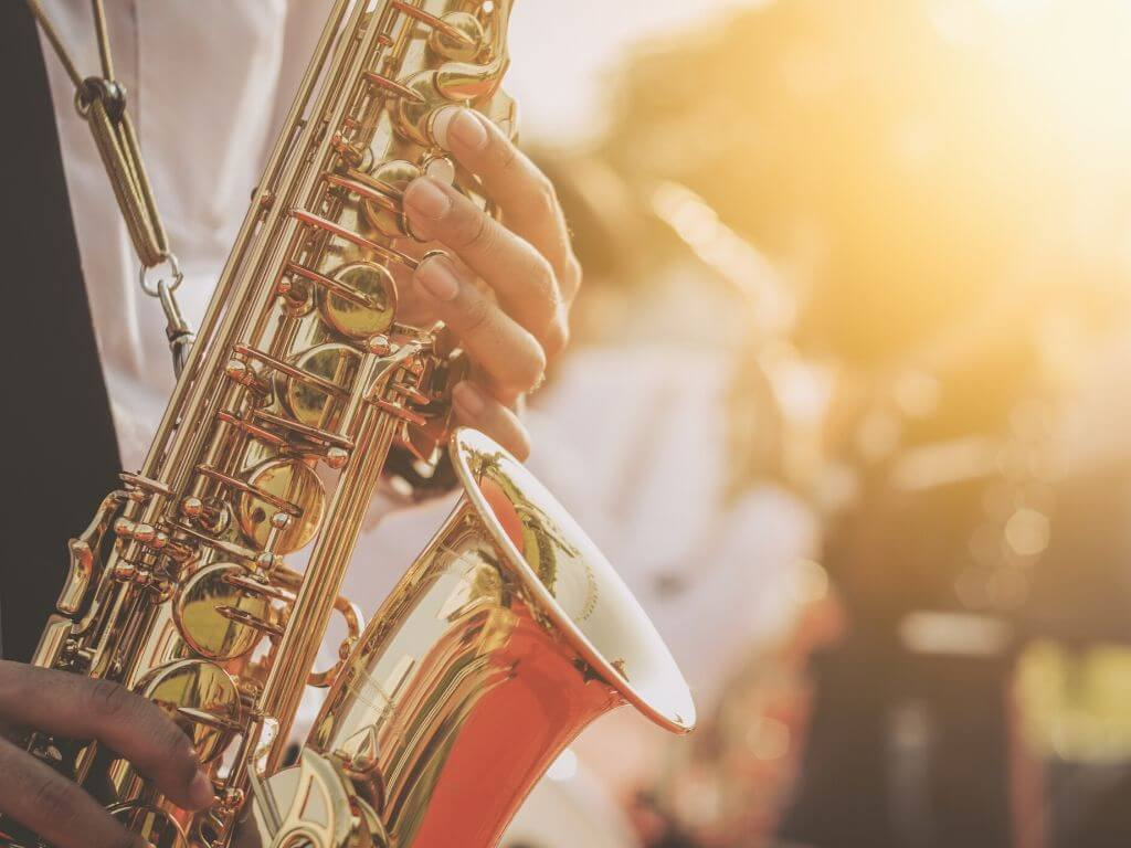 A picture of a saxaphone at a jazz festival illuminate by golden sunlight