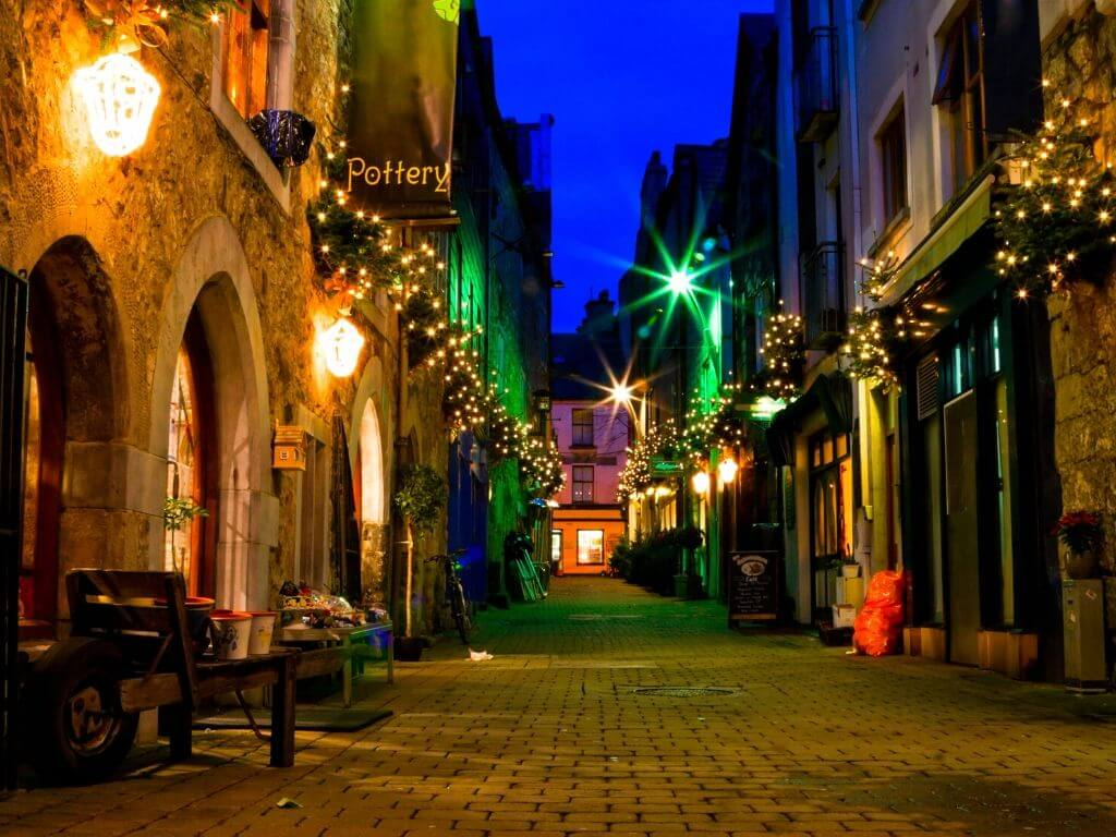 A night time shot of a narrow street lit by lights in Galway City, Ireland