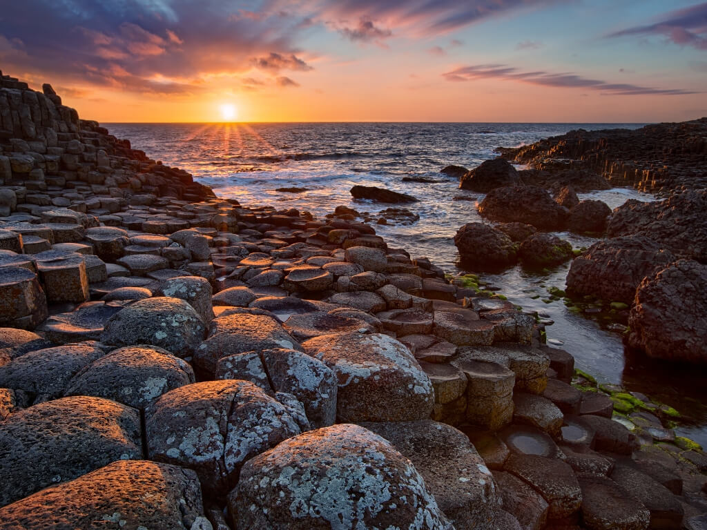 A sunset picture of the Giant's Causeway columns at the water's edge in Northern Ireland