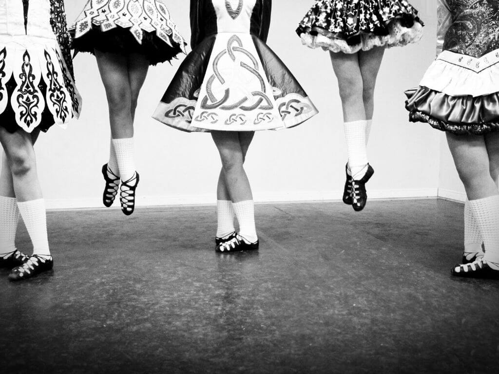 A black and white picture of the legs and feet of five Irish dancers in their dance shoes, socks and part of the skirt of their dresses showing