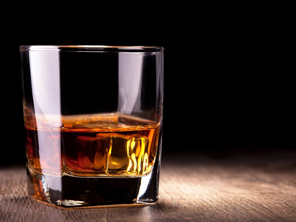 A picture of a glass of Irish Whiskey on a wooden table with a black background