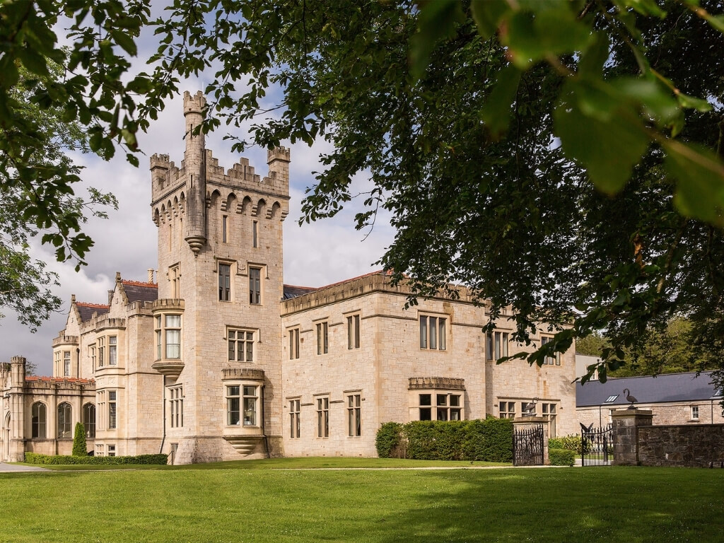 A picture of Lough Eske Castle through some tress, one of the best castles to stay in Ireland
