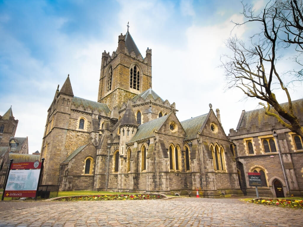 A picture of Christ Church Cathedral in Dublin with cloudy but blue skies above it.