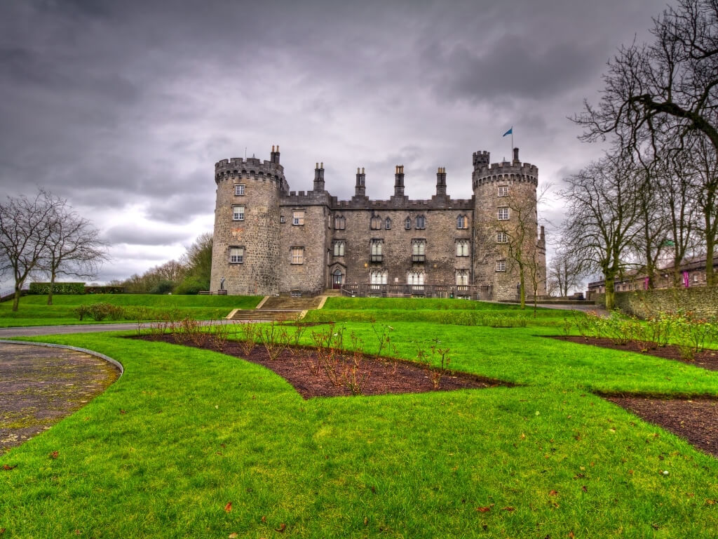 A picture of Kilkenny Castle with lush green grass in front and a grey, stormy sky behind it