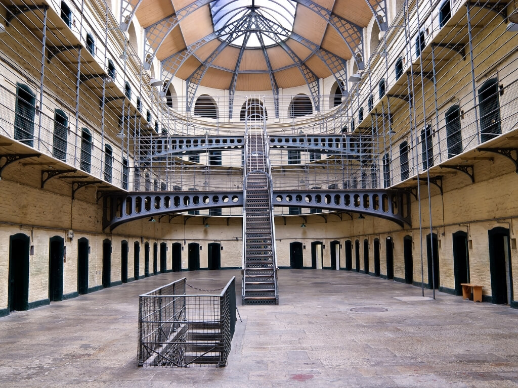 A picture inside Kilmainham Gaol, Dublin, Ireland, with cell door centred around an atrium with two levels of metal stairs and balconies