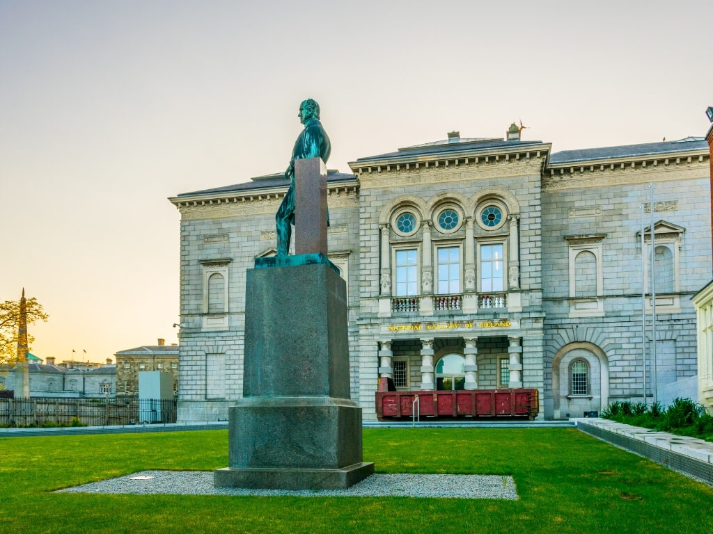 A picture of a statue outside the National Gallery of Ireland with the main building in the background