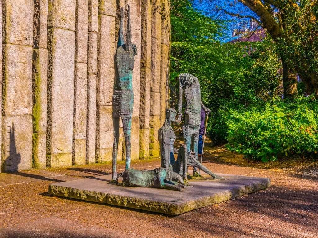 Three statues with a sleeping dog at one of the entrances to St Stephen's Green in Dublin, Ireland