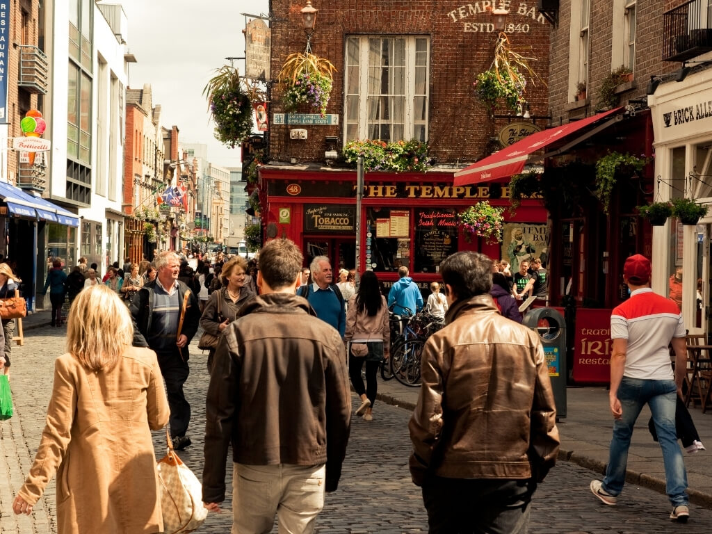 A picture of a busy street in Dublin's Temple Bar with people walking along the street and entering pubs