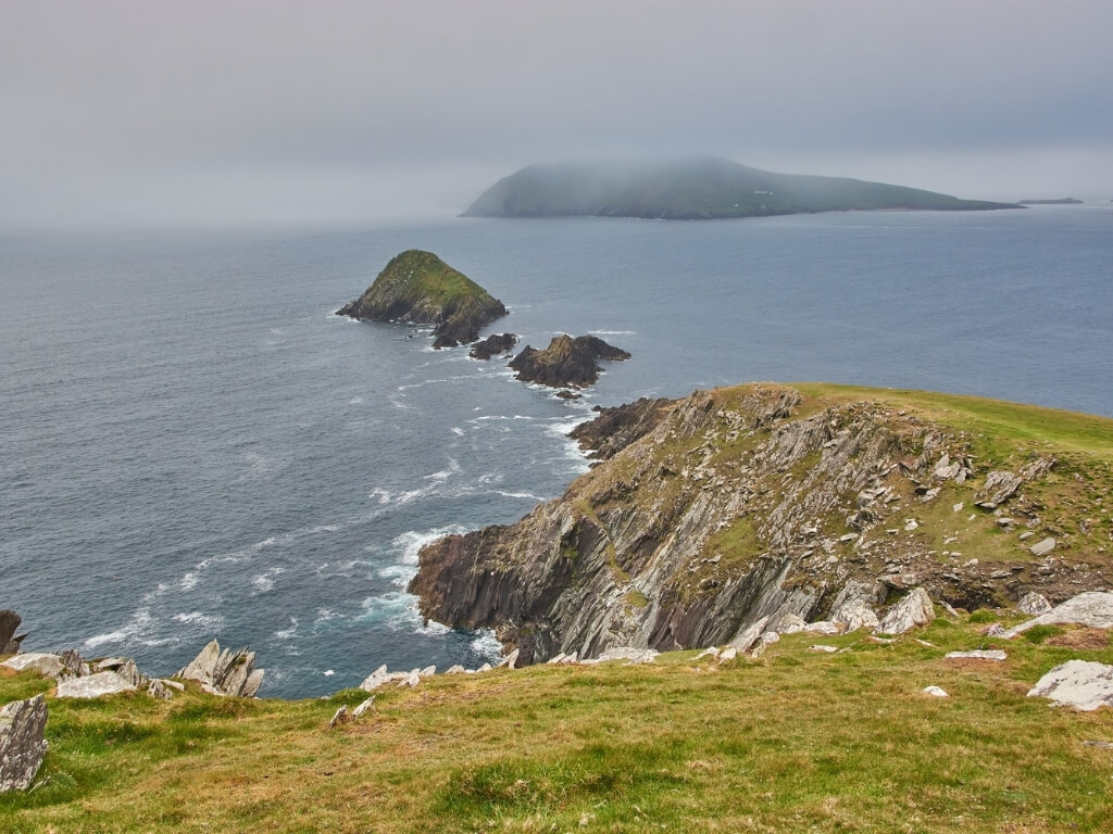 A picture of mist and stormy weather over an island off the rugged coastline of the Dingle Peninsula in Ireland