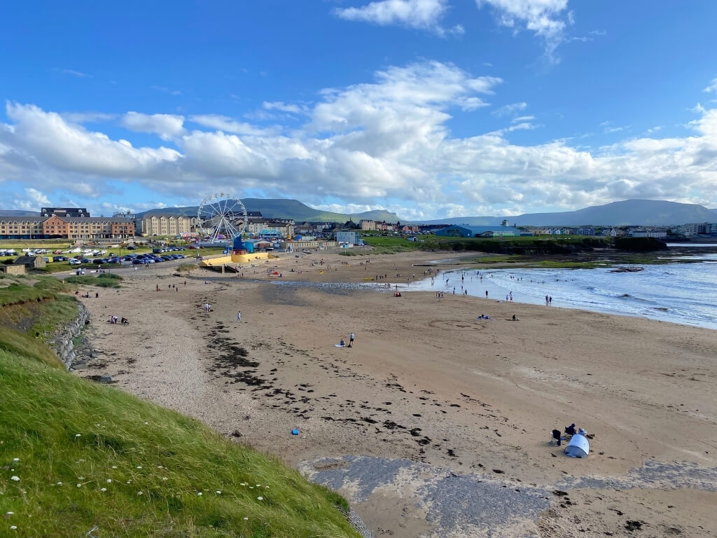 A picture of the golden sandy beach at Bundoran, Donegal with people on the beach and in the sea in the background. To the left is green hills and the ferris wheel at Bundoran and to the right is the white sea and mountains in the background