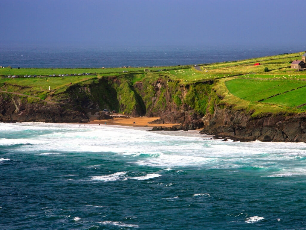 A picture of a rough sea with white waves crashing in the foreground, leading to a sandy beach surrounded by dark sheer cliffs which are topped with rolling lush green grass over. In the background there is another stretch of dark blue sea under dark stormy skies. This beach is Coumeenoole in Kerry, Ireland
