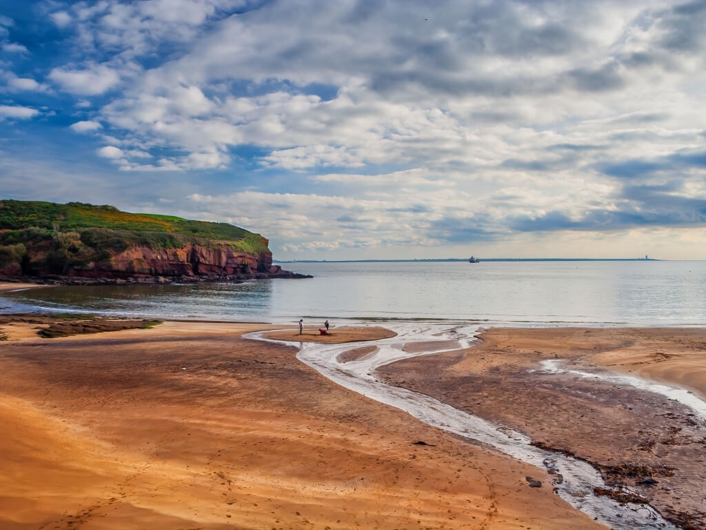 A picture of the sandy beach at Dunmore East with red cliffs on the left topped with green grass, a patchy blue sky in the background and a tidal stream of water in the foreground on the right, Three people are at the shoreline on the sand