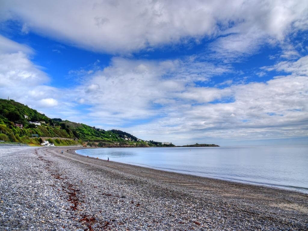 a picture of the stony beach at Killiney, looking towards Killiney Head with a calm sea in the foreground and blue skies overhead