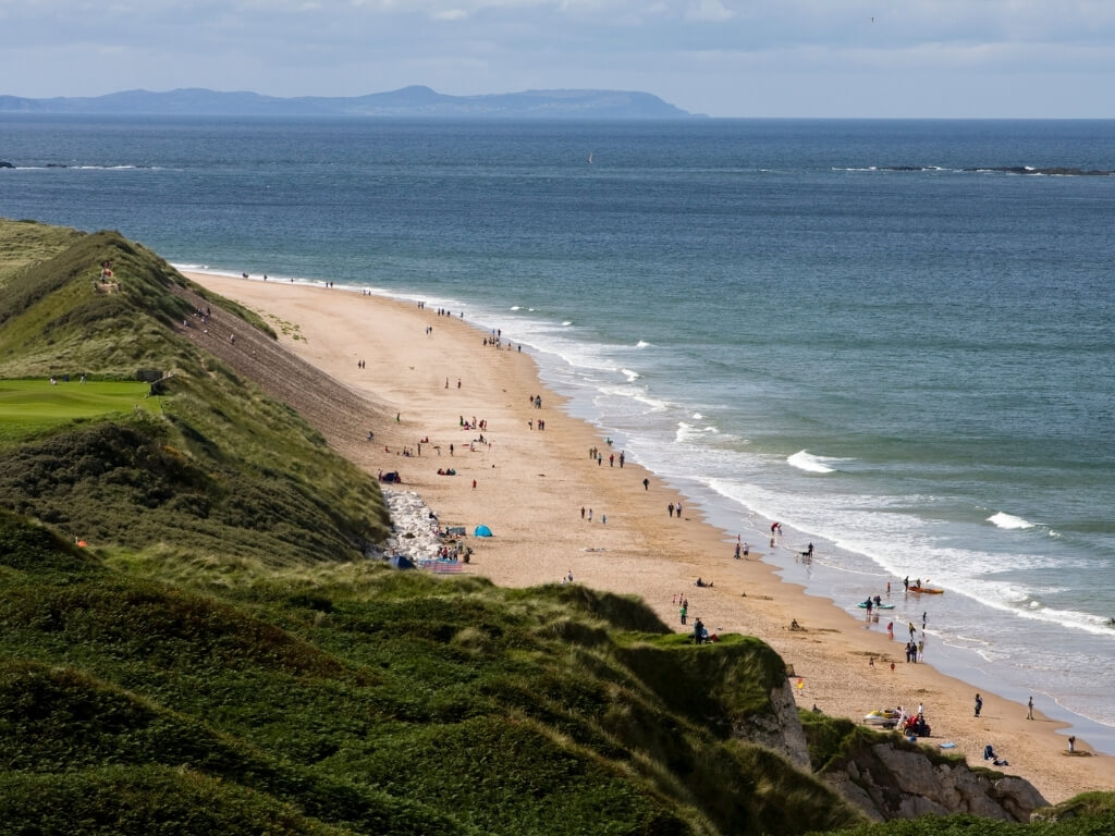 A picture of Whiterocks Beach with walking along the shoreline on the right of the picture and rolling, grassy hills and dunes leading to the sandy beach on the left
