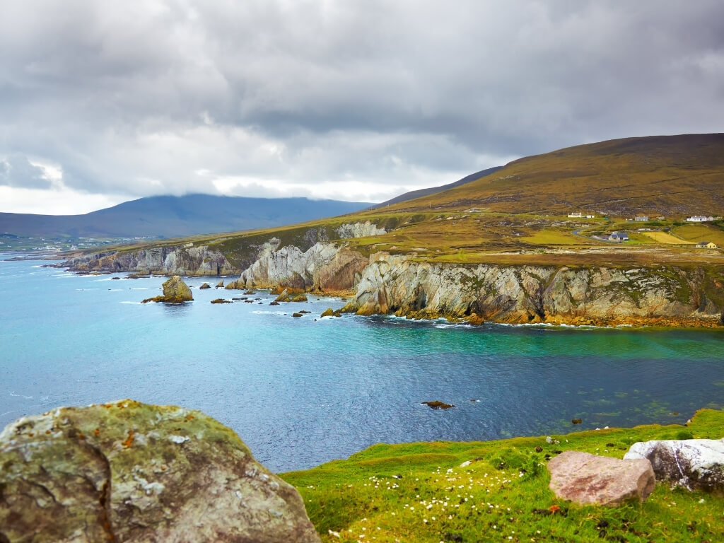 Achill Island coastline with blue waters, green hills leading down to the water's edge and grey clouds in the sky