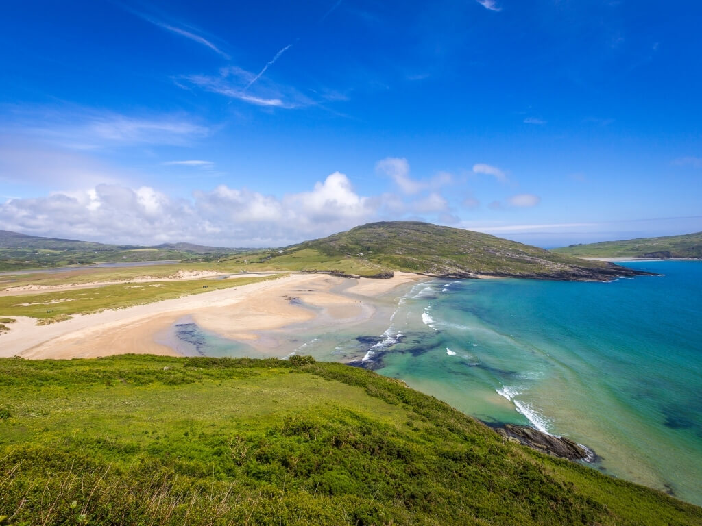 A picture of the beach and shoreline of Barleycove Beach in cork with turquoise sea and green grassy hills around it