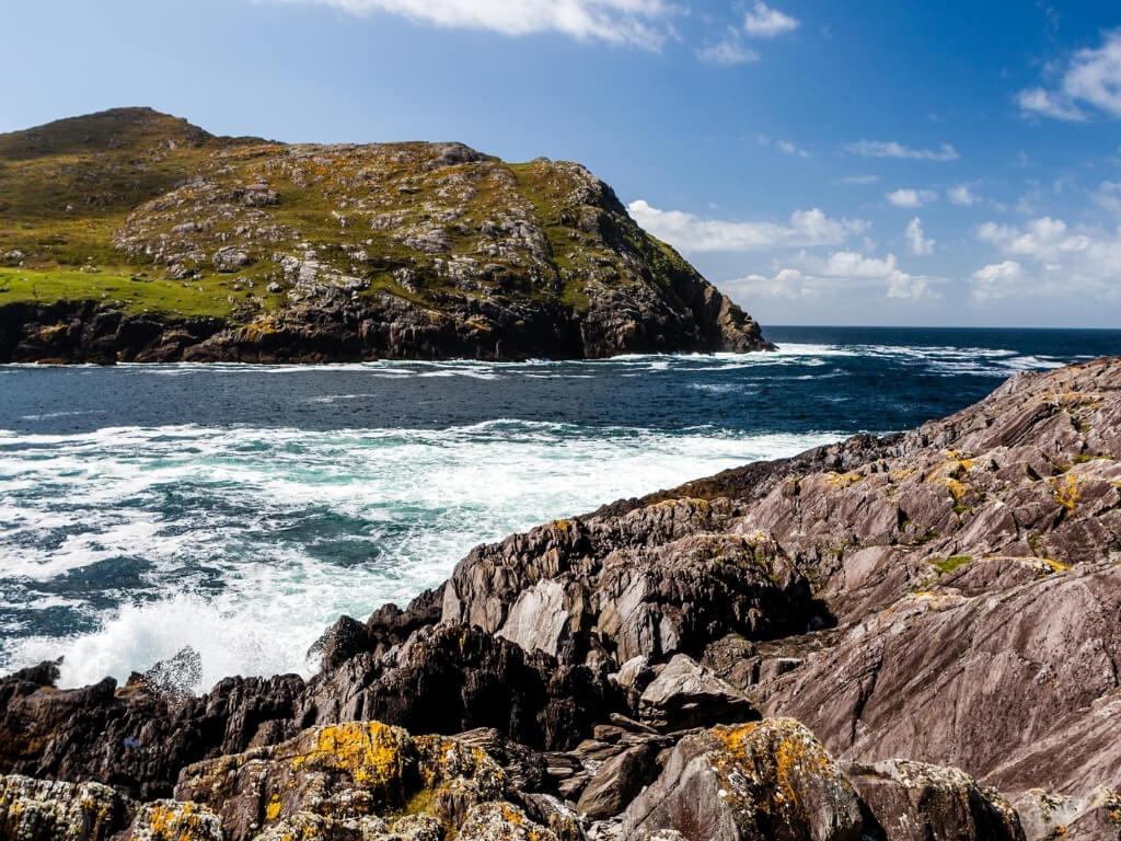 A rugged coastal scene with jagged rocks and white waves on the Beara Peninsula in County Cork, Ireland