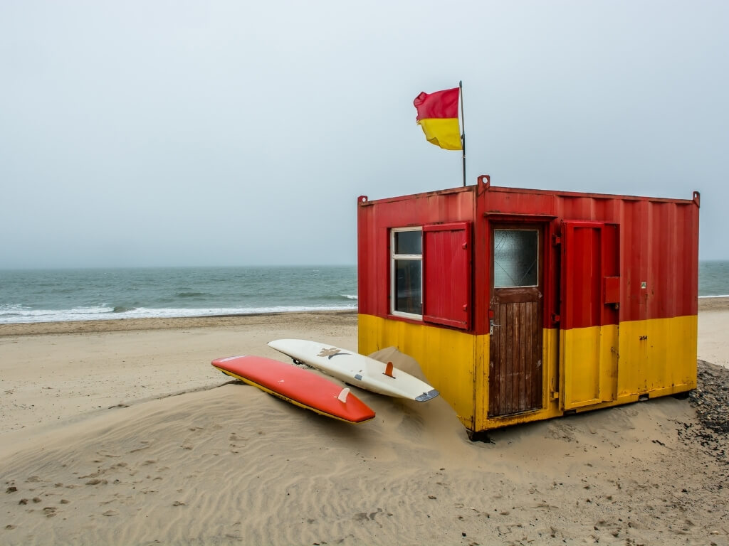 A picture of a red and yellow lifeguard house on the sandy beach of Brittas Bay with grey skies over the sea