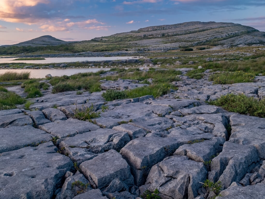 A picture of the unique grey limestone landscape of the Burren National Park with patches of green grasses and hills in the background