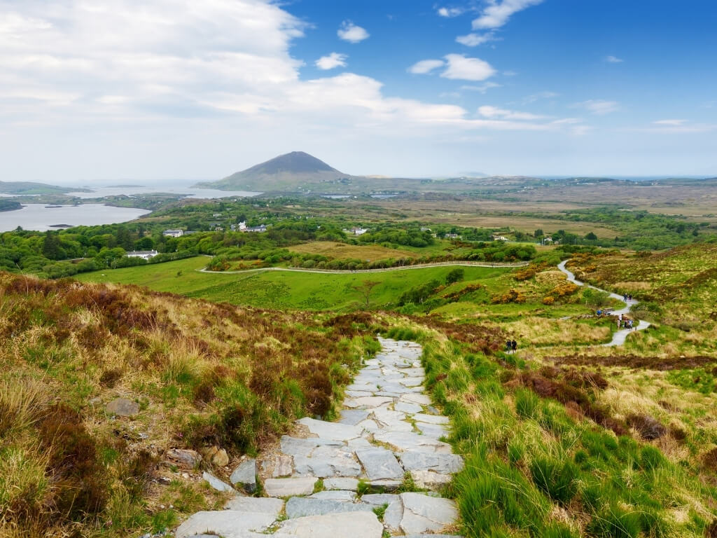 A view from the Diamond Hill Coastal Trail in Connemara National Park with a stoney path weaving its way through rolling fields and a sugar-loaf mountain in the background leading down to a lake