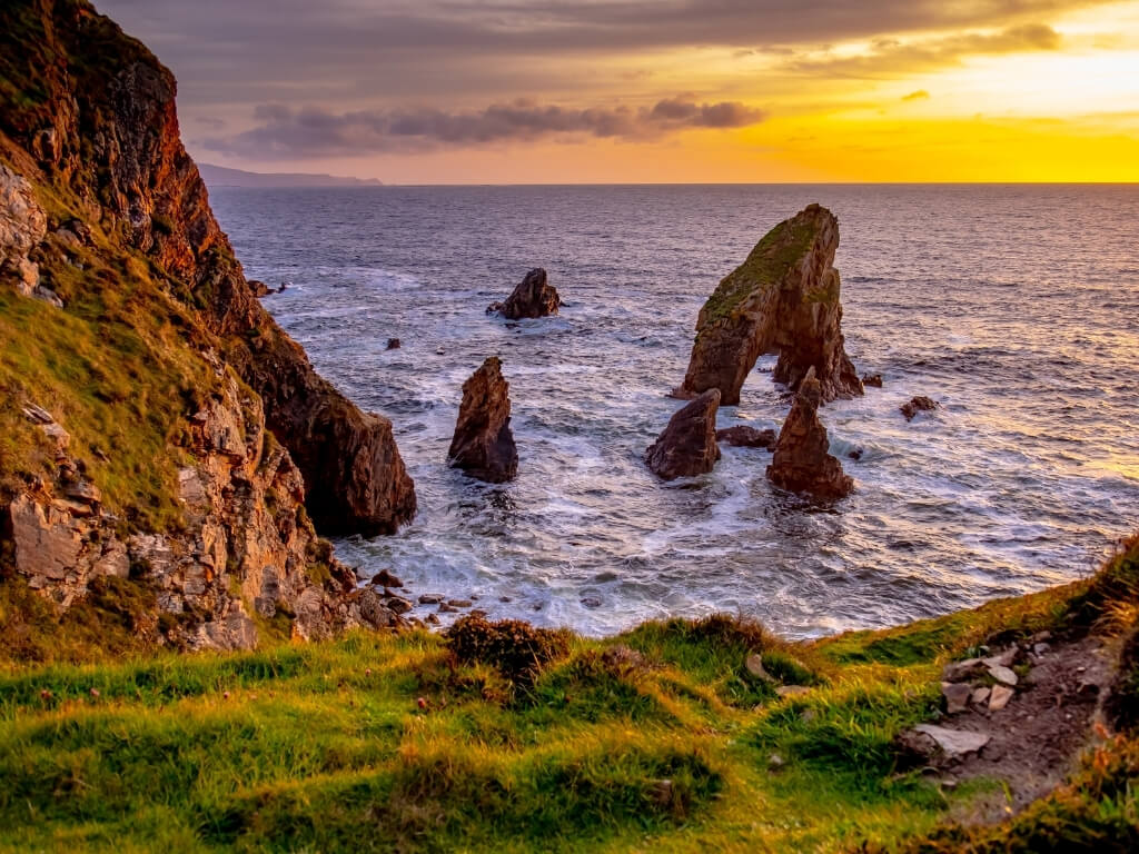 A picture of the sun setting over the Donegal coast of Ireland with the Crohy sea arch in the foreground and craggy rocks to the side