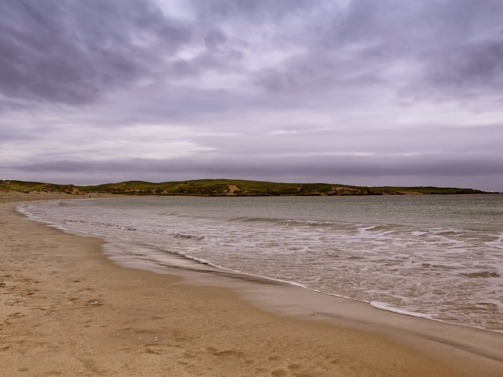 A picture of a grey, menacing sky overhead and the sandy beach of Dog's Bay in the foreground with green hills in the background