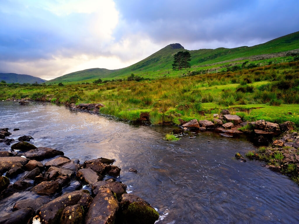 A picture of the Erriff River in County Mayo, Ireland with lush green hills in the background and the river in the foreground