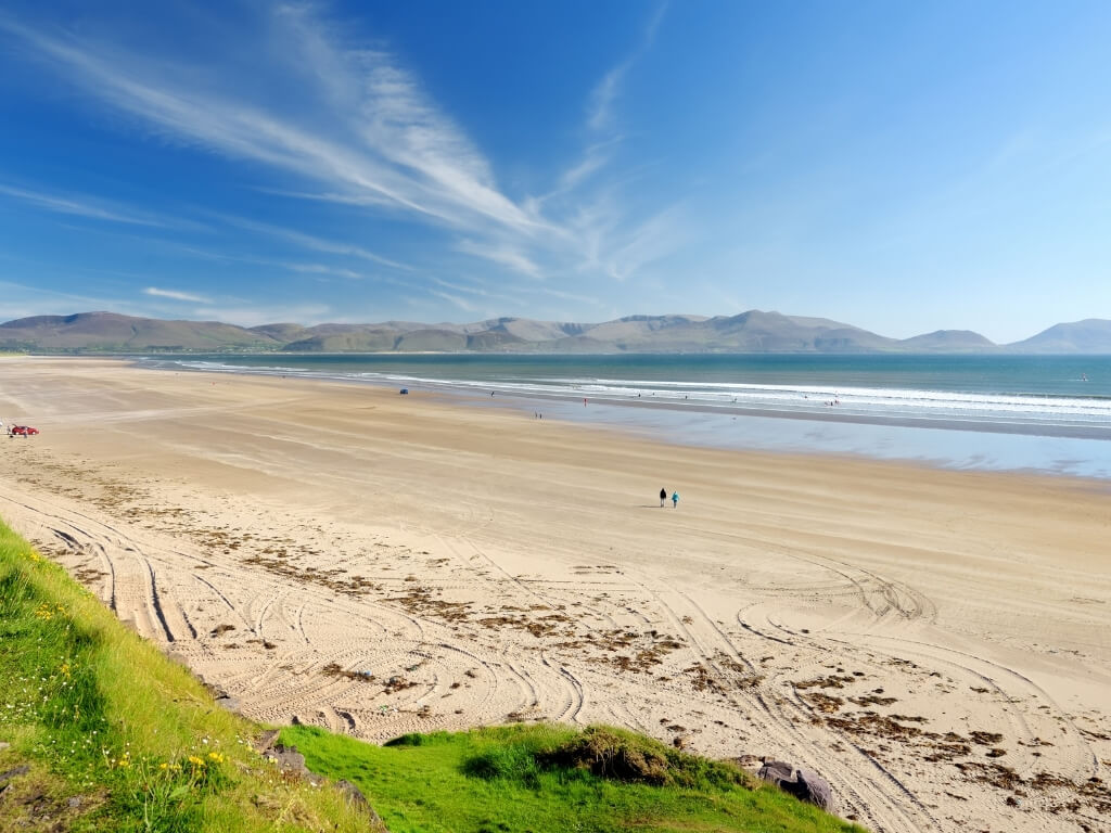 A picture of th elong sandy beach at Inch on the Dingle Peninsula in Ireland with two people walking along it and blue skies overhead