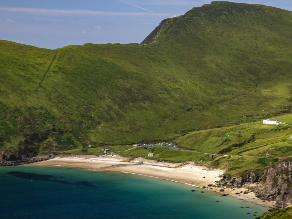 a picture of the horseshoe bay of Keem with green hills in the background leading down to the sandy beach with green/blue sea in the foreground