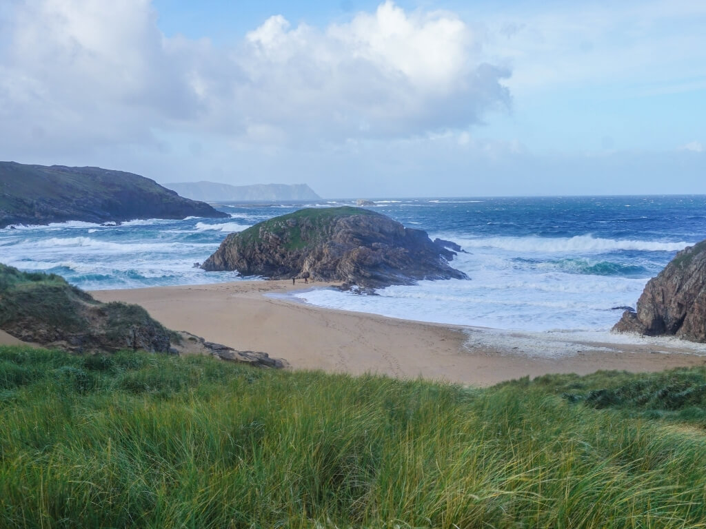 A picture of the island that separates the two stretches of beach at Murder Hole in Donegal, with rough waves crashing around it in the background and green grass in the foreground leading to the sandy beach in the middle of the picture