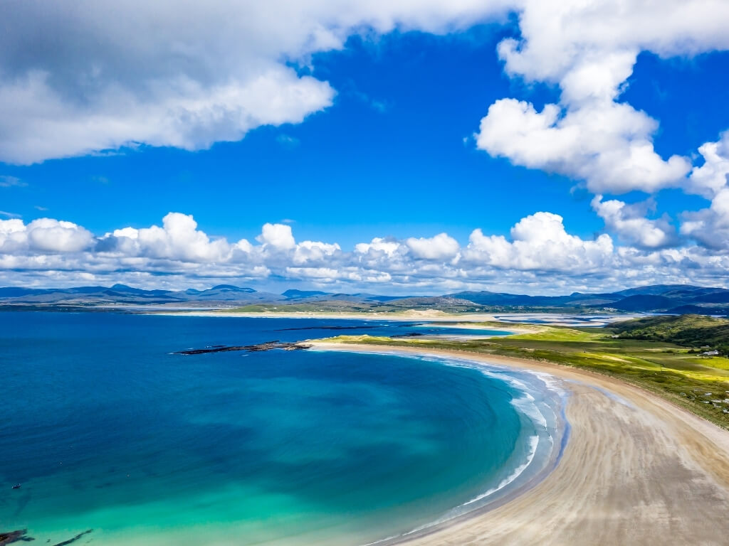 A picture of the blue sea at Narin Beach in the left hand corner of the picture leading to the almost white sandy beach on the right and green fields and hills in the background and blue skies above