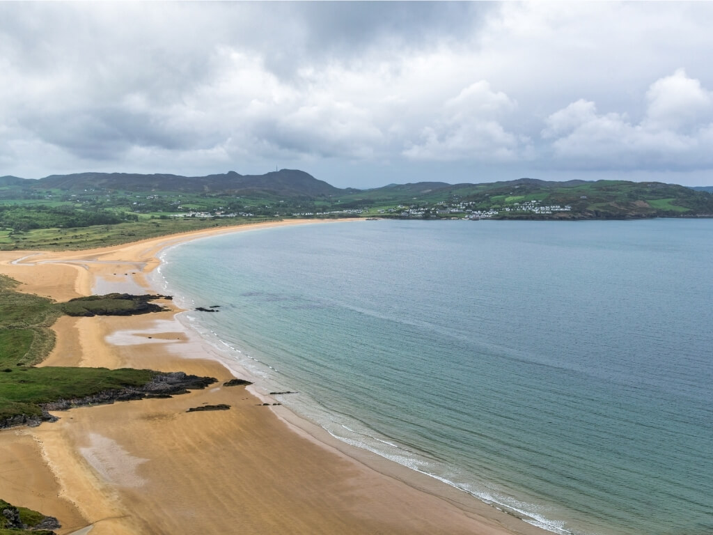 A picture of a golden sandy beach at Portsalon, Donegal with an expanse of calm sea and hills in the background