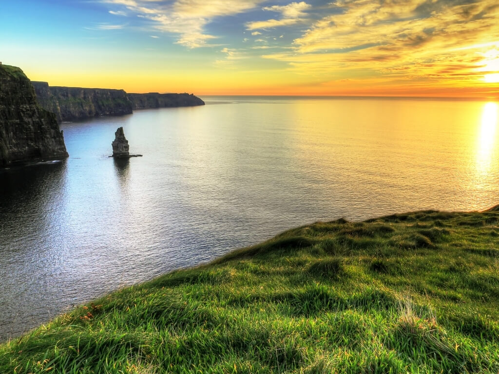 A picture of the sun setting in the distance, lighting up the Cliffs of Moher along Ireland's Wild Atlantic Way.