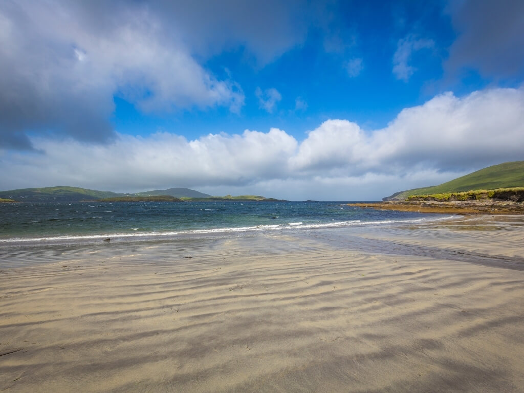 A picture of Whitestrand beach, Kerry, one of the best beaches in Ireland, with a sandy shore in the foreground, blue sea and mountains in the background and blue skies with white fluffy clouds