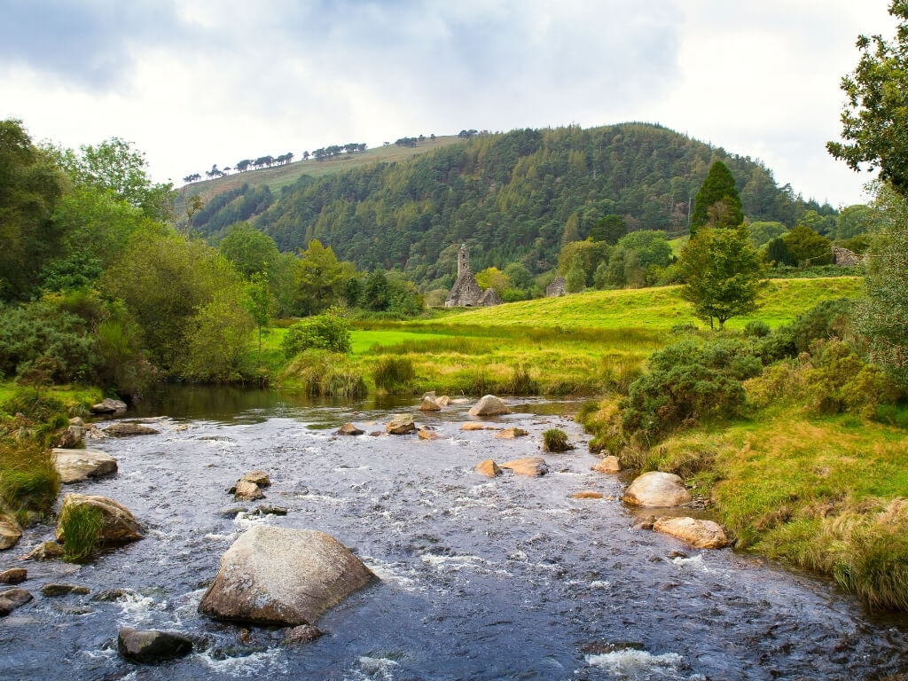 A picture of a stream in the foreground and the Round Tower of Glendalough in the background with wooded hills behind it in the Wicklow Mountains National Park in Ireland