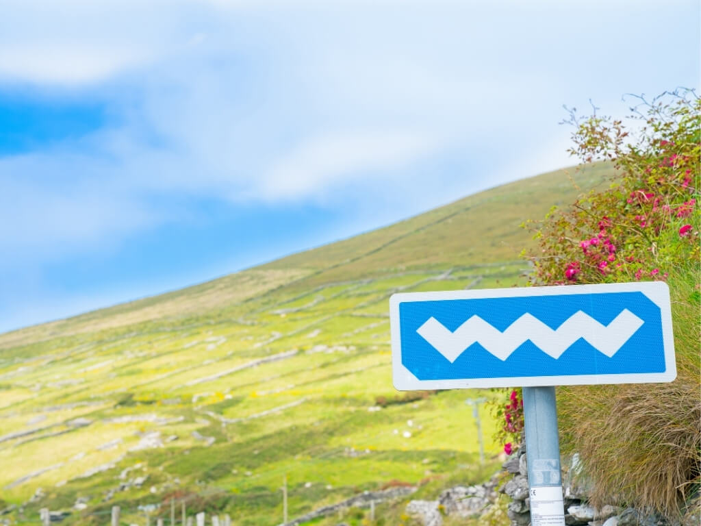 A blue Wild Atlantic Way road sign in Ireland with grassy hills behind it