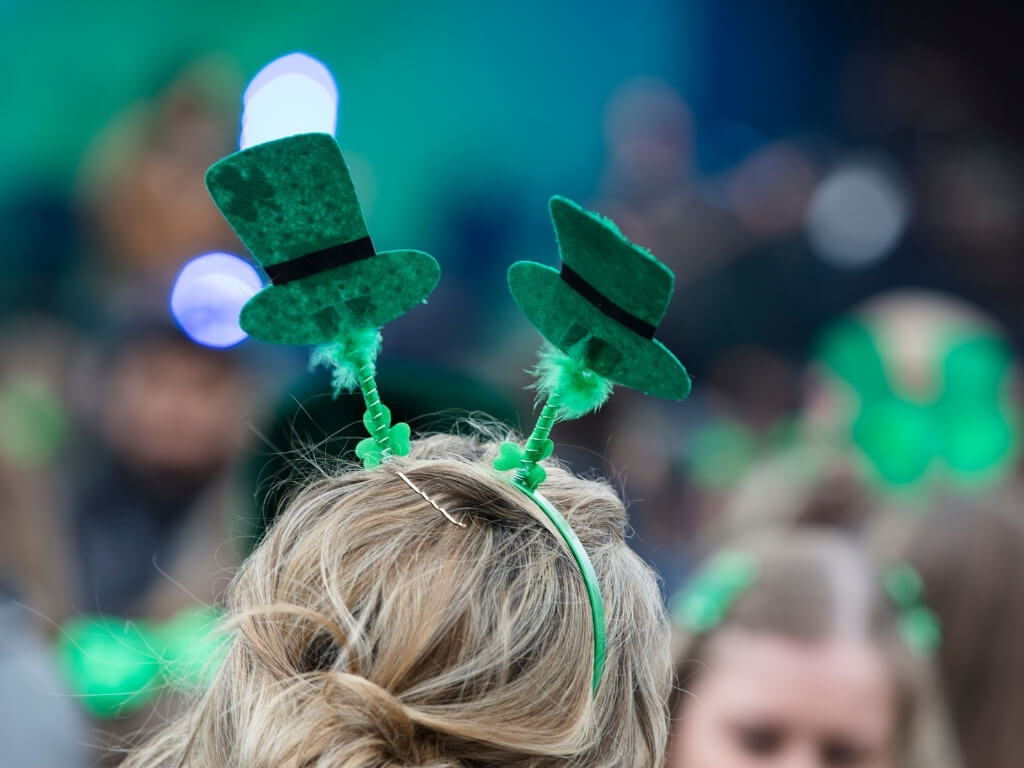 A picture of a headband on a woman's head with two green leprechaun hats on it for celebrating St Patrick's Day in Ireland