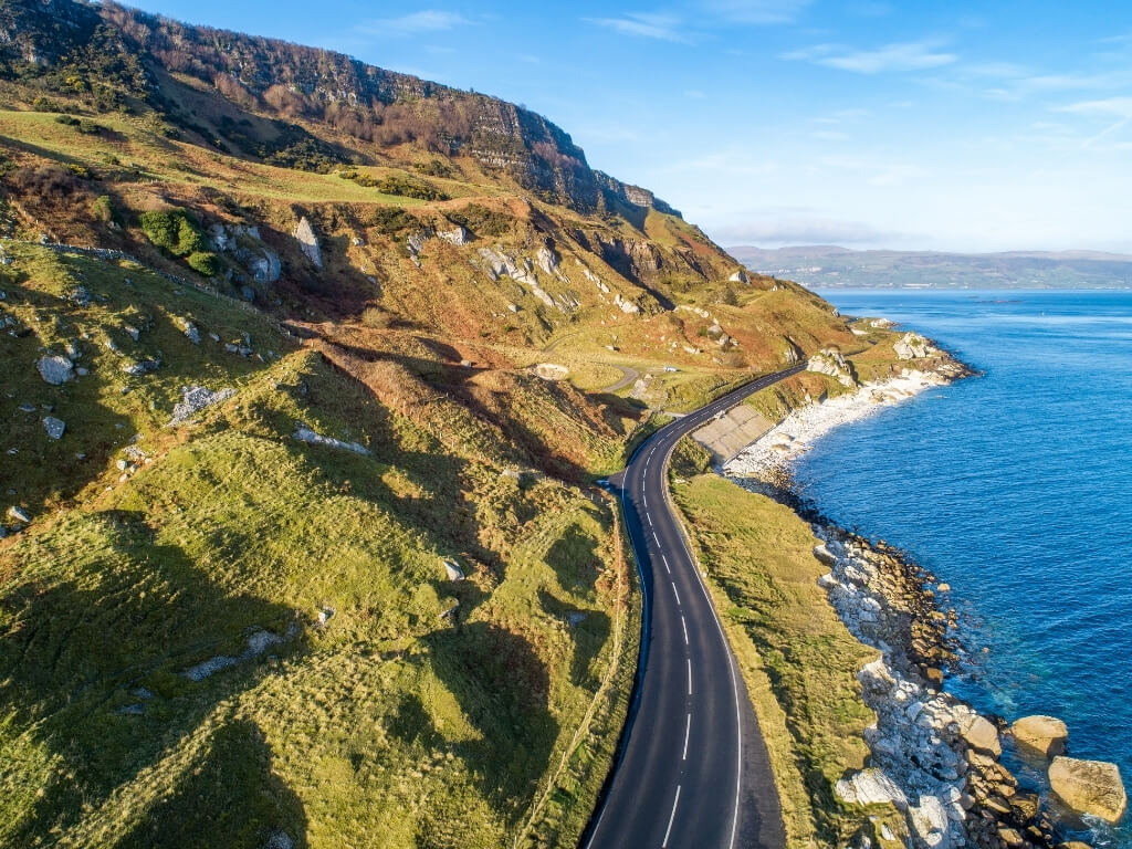 A picture of a road following a coastline, which is the Antrim Coast Road in Northern Ireland