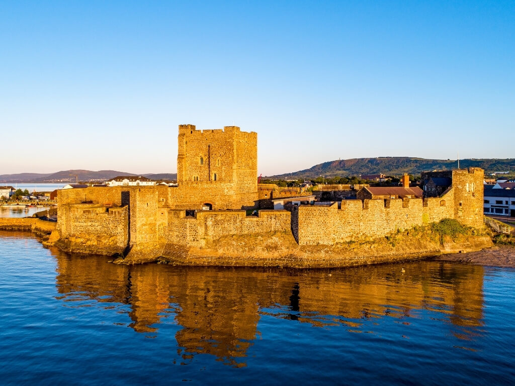 A picture of Carrickfergus Castle at the shoreline bathed in golden sunlight with blue skies overhead