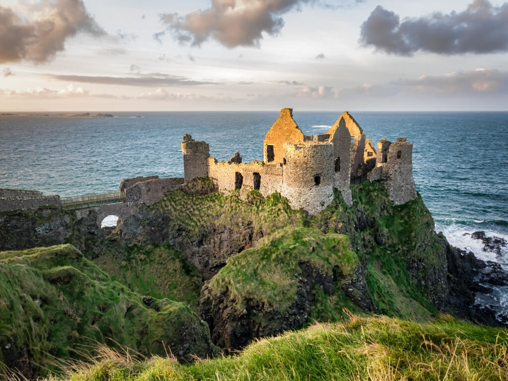 A picture of the ruins of Dunluce Castle on the Causeway Coast in Antrim with sunlight bathing it and the sea in the background