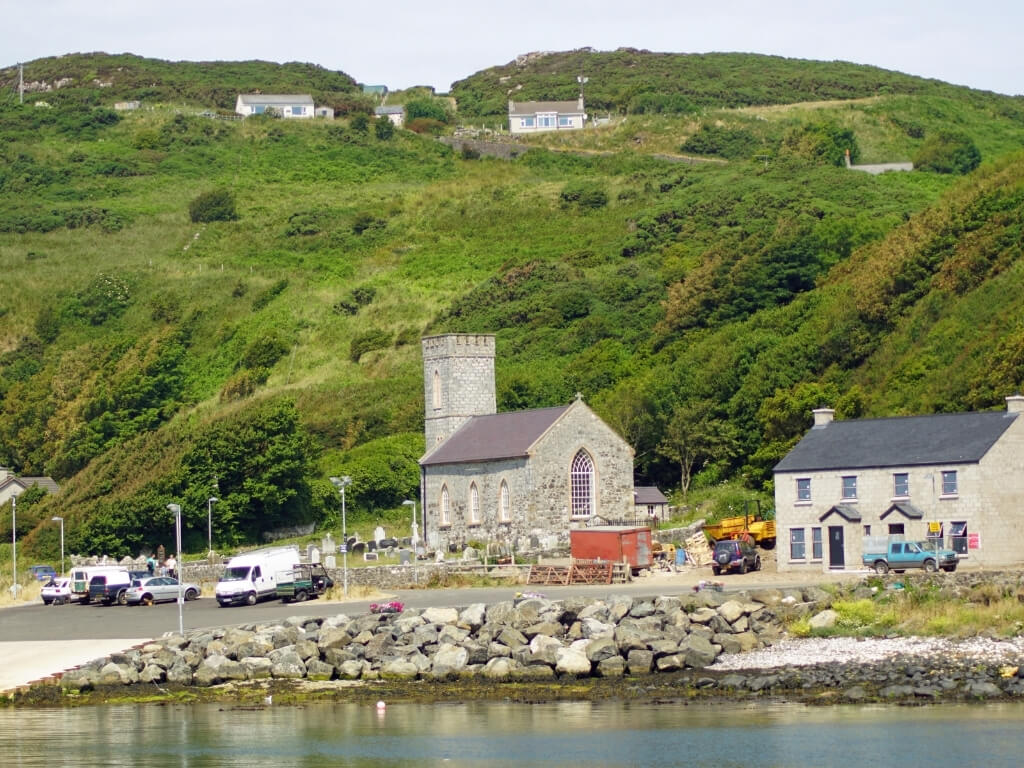 A picture of buildings at the harbour side on Rathlin Island, Antrim with a green grassy hill in the background