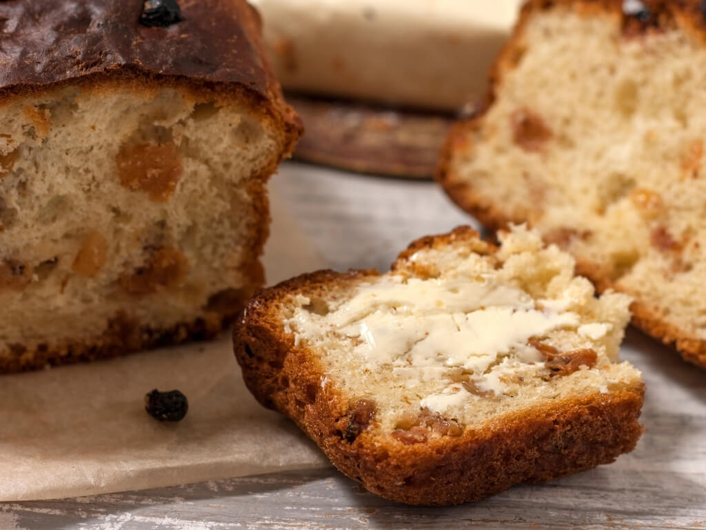 A picture of Irish Barmbrack, sliced with butter on it