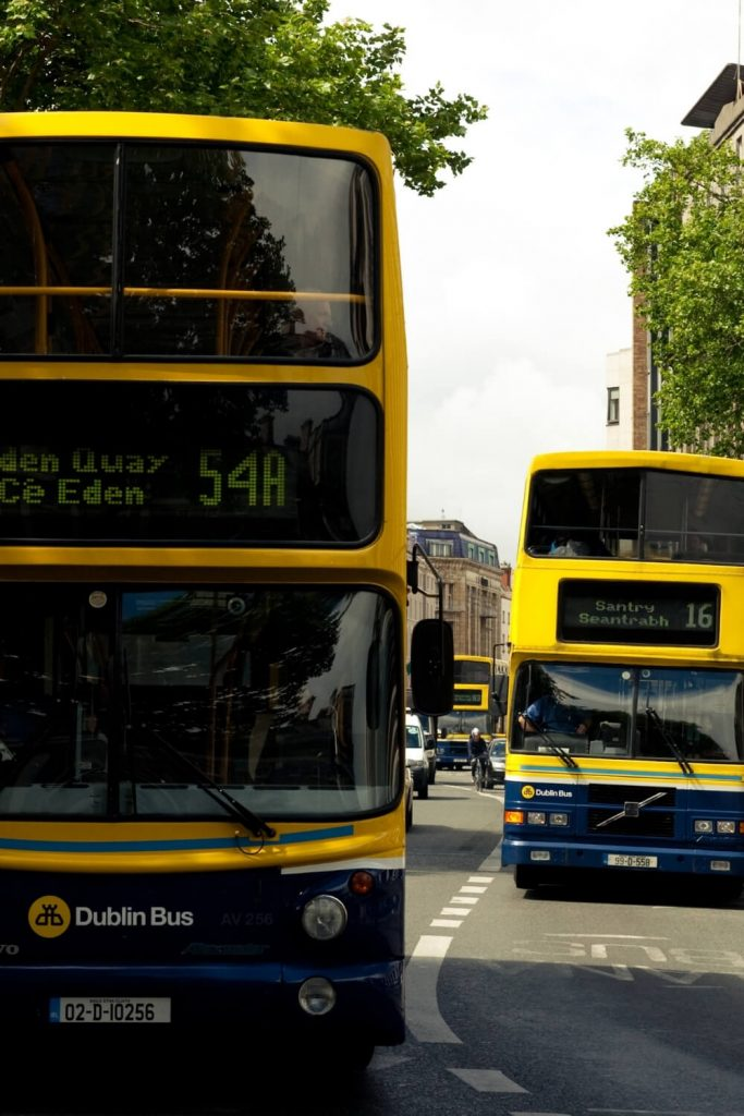 A picture of two Dublin buses, the number 16 and the number 54A travelling on a road in Dublin