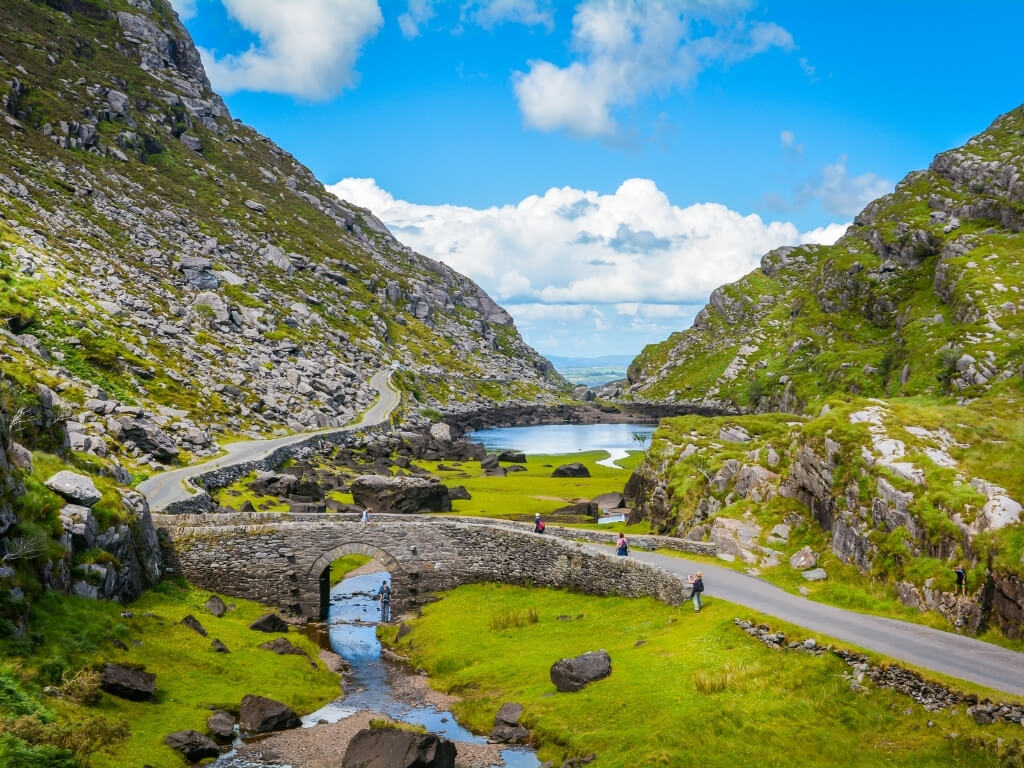 A picture of people crossing a bridge in the Gap of Dunloe in Ireland on a sunny day
