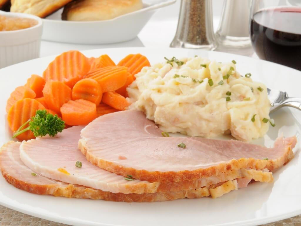 A picture of a plate containing slices of boiled ham, mashed potato, carrots and broccoli