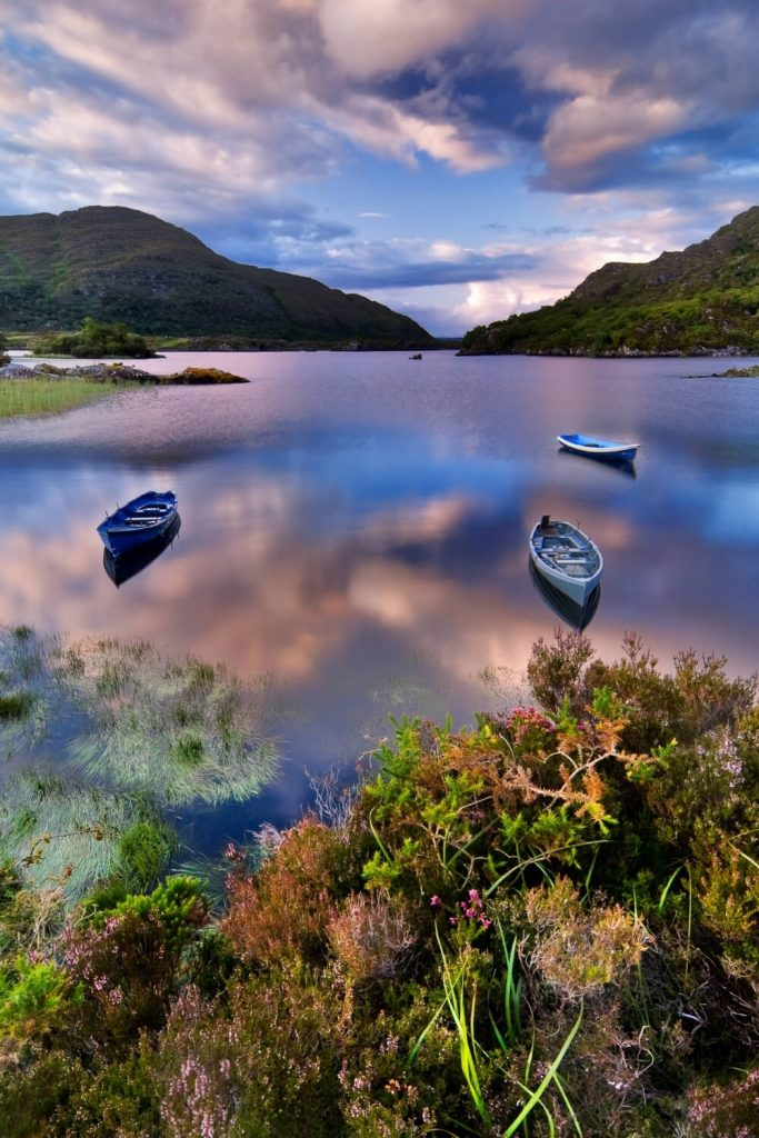 A picture of three boats moored on a still lake in the Killarney National Park