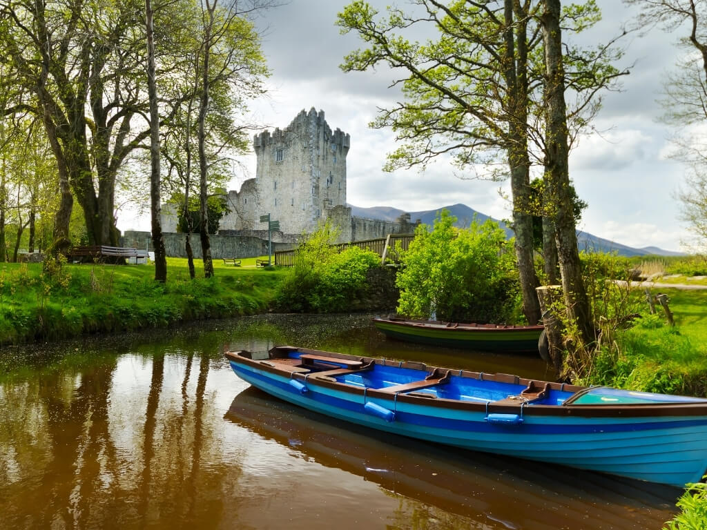 A picture of a blue boat on a lake with Ross Castle in the background, found in the Killarney National Park